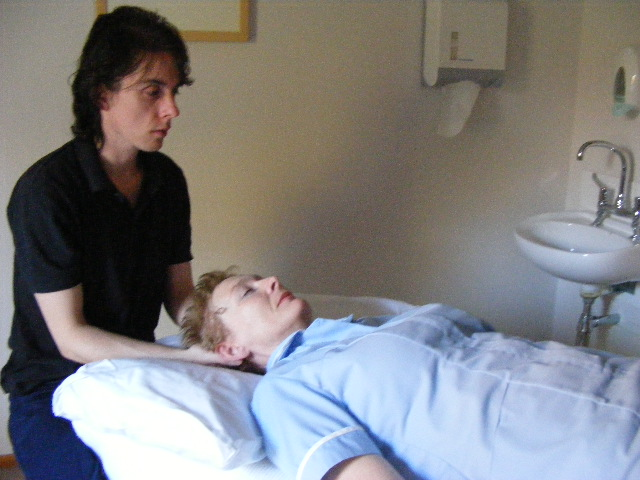 Therapist performing Visceral Manipulation Technique therapy on a woman's neck and shoulders