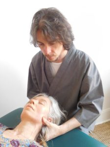Patient lying on table getting treated with Craniosacral therapy in Glasgow